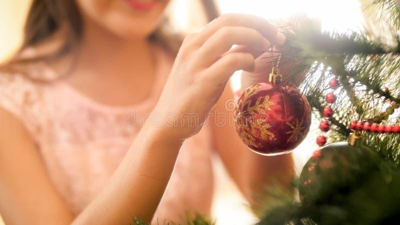 Immagine del primo piano dell'adolescente che decora l'albero di Chrismtas con le bagattelle rosse immagini stock