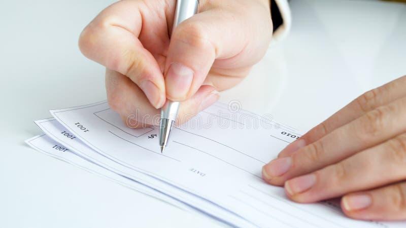 Immagine del primo piano dell'assegno di firma di attività bancarie della mano femminile fotografia stock libera da diritti