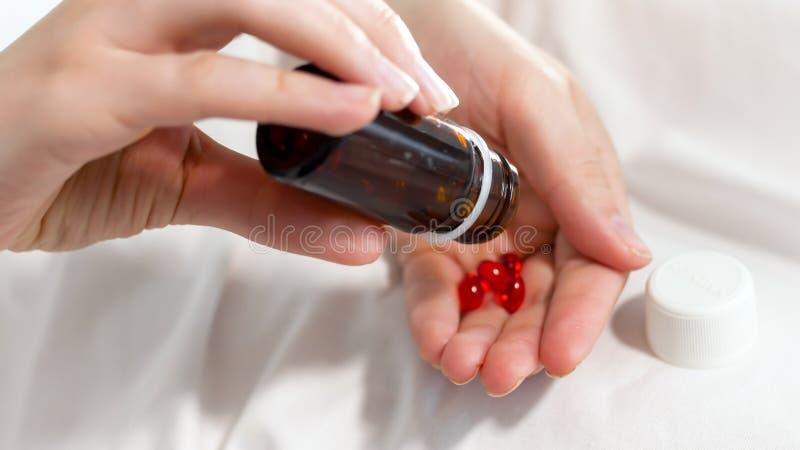 Immagine del primo piano della bottiglia paziente femminile della tenuta delle pillole e di agitazione  fotografie stock libere da diritti