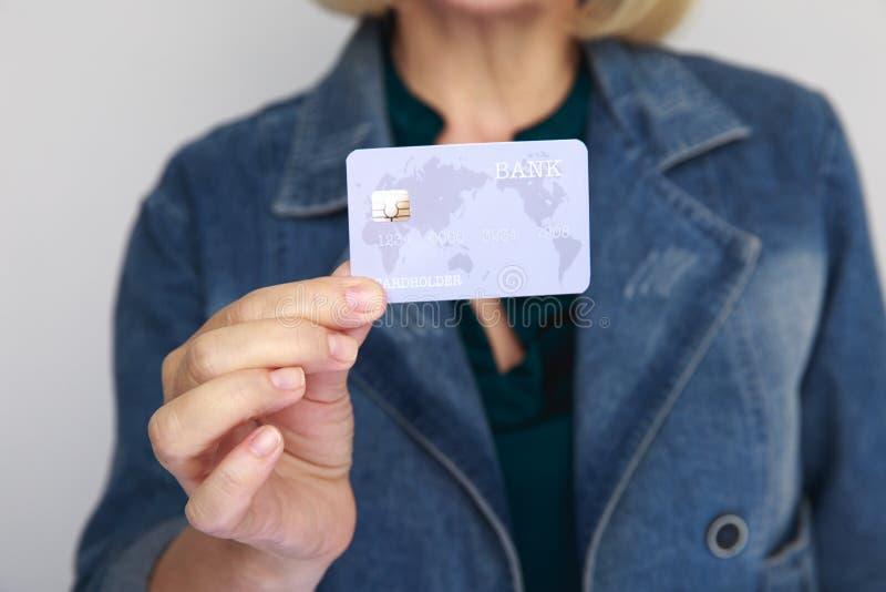 Immagine del primo piano della carta di credito in mano di una donna isolata in uno studio fotografia stock
