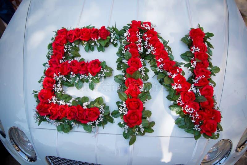 Immagine del primo piano della decorazione dell'automobile di nozze con il mazzo dei fiori rossi e bianchi immagini stock libere da diritti