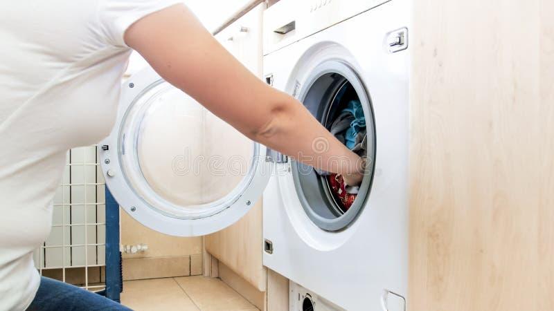 Immagine del primo piano della giovane donna che spinge grande mucchio dei vestiti in lavatrice immagine stock libera da diritti