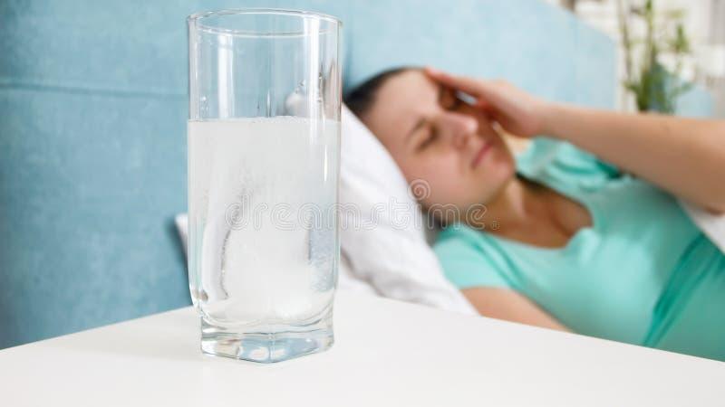 Immagine del primo piano della pillola di aspirin che si dissolve in bicchiere d'acqua sul comodino fotografia stock libera da diritti