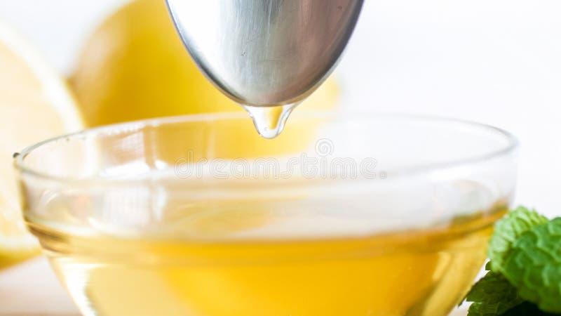 Immagine del primo piano della sgocciolatura del miele dal cucchiaio del metallo fotografia stock