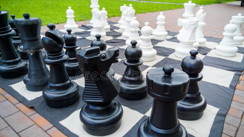 Immagine del primo piano delle figure giganti di scacchi e della scacchiera in parco Spettacolo e divertimento per la famiglia al fotografia stock