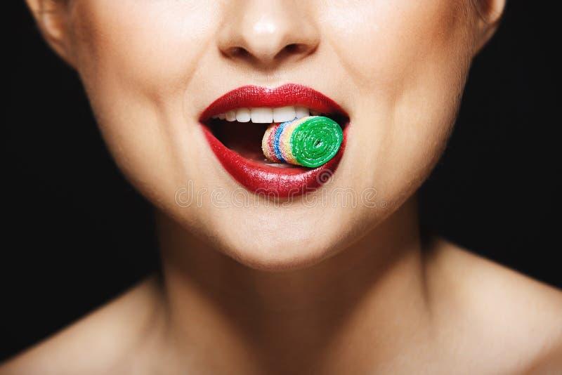 Immagine del primo piano delle labbra allegre del ` s della ragazza che tengono i tesori con i denti fotografia stock