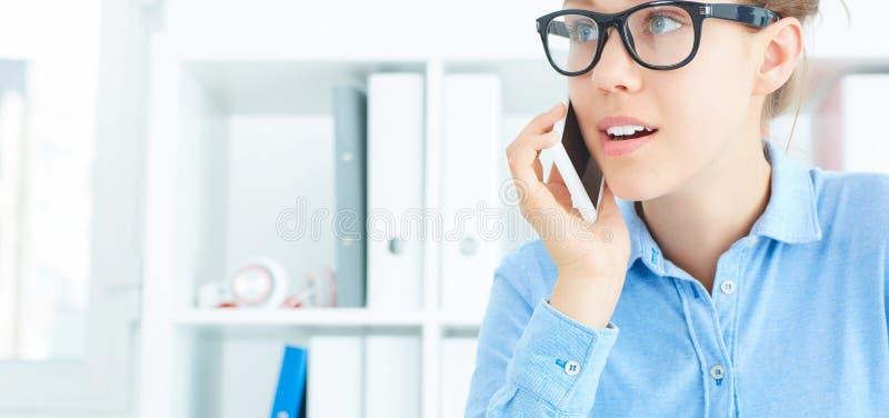 Immagine del primo piano di bella ragazza sorridente che parla sul telefono cellulare nell'ufficio fotografie stock