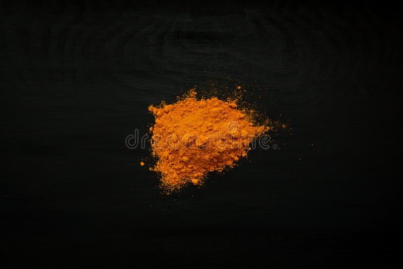 Immagine del primo piano di curcuma, polvere della curcuma su fondo di legno nero, vista qui sopra fotografia stock