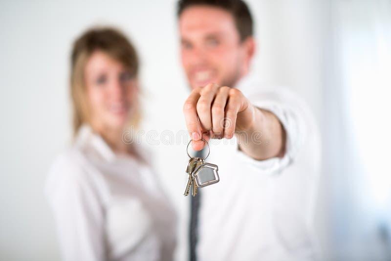 Immagine del primo piano di giovani chiavi allegre della casa della tenuta delle coppie di agente immobiliare immagine stock libera da diritti