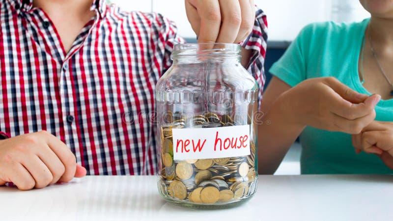 Immagine del primo piano di giovani soldi di risparmio della famiglia per l'acquisto della casa nuova fotografie stock libere da diritti