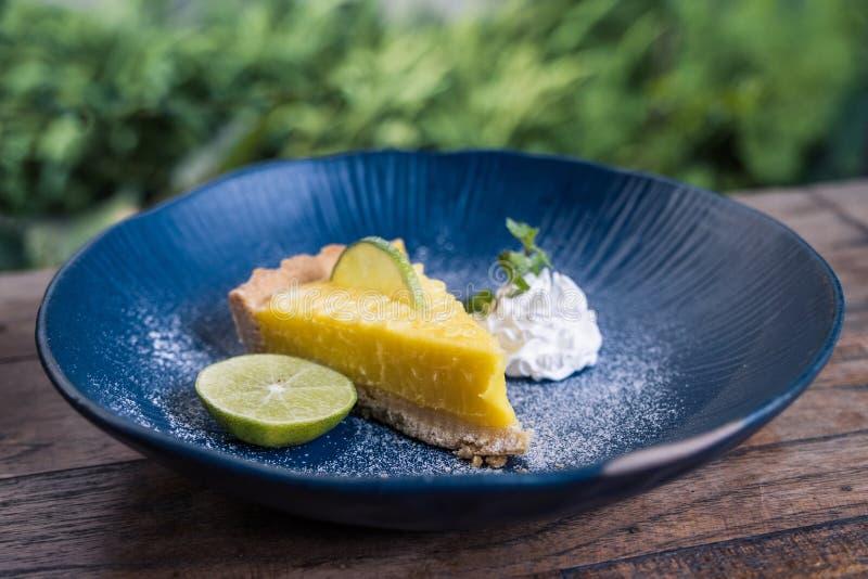Immagine del primo piano di un dolce giallo della cagliata di limone in piatto ceramico blu sulla tavola di legno immagine stock libera da diritti