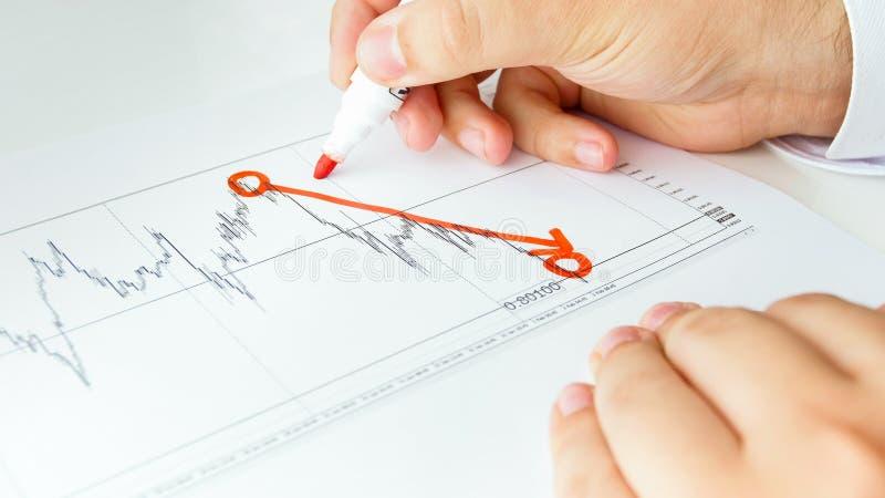 Immagine del primo piano del disegno dell'uomo d'affari che fa diminuire grafico finanziario fotografie stock