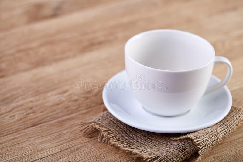 Immagine del primo piano del fuoco selettivo del tazza da the e del piattino bianchi vuoti su fondo d'annata rustico con il tovag immagini stock libere da diritti