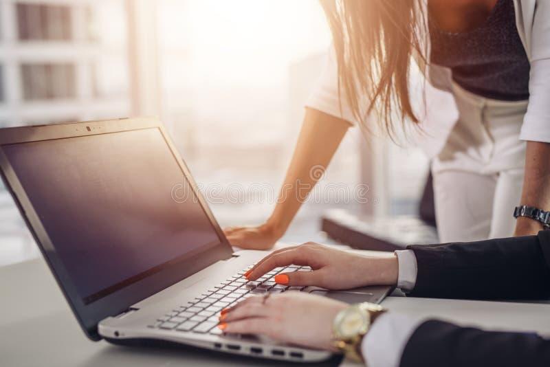 Immagine del primo piano del gruppo creativo facendo uso di Internet che scrive sulla tastiera del computer portatile nell'edific immagini stock