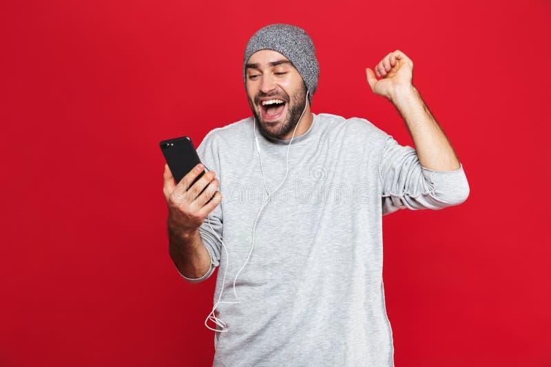 Immagine del telefono cellulare unshaved e di ascoltare della tenuta dell'uomo la musica con le cuffie isolate sopra fondo rosso immagini stock