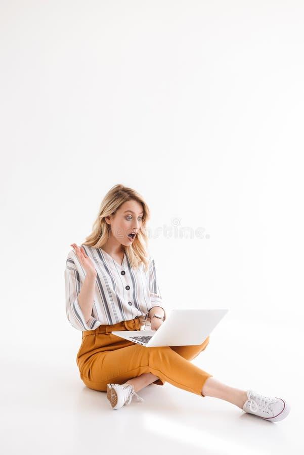 Immagine dell'abbigliamento casual d'uso della bella donna emozionante che esamina computer portatile mentre sedendosi sul pavime immagini stock libere da diritti