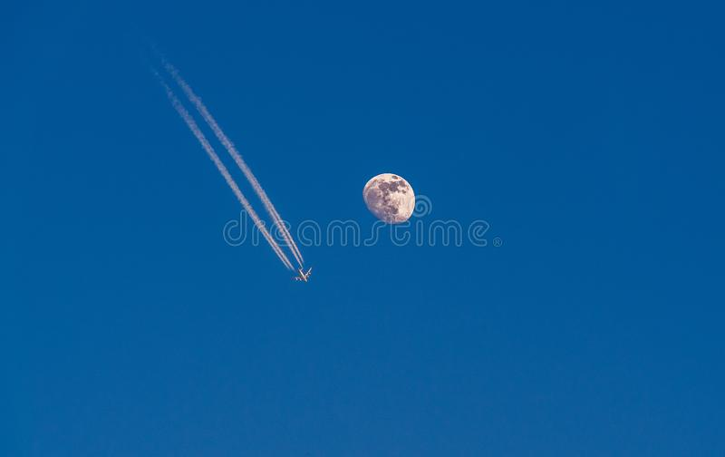Immagine dell'aeroplano con le scie di condensazione che volano accanto alla luna dettagliata immagini stock