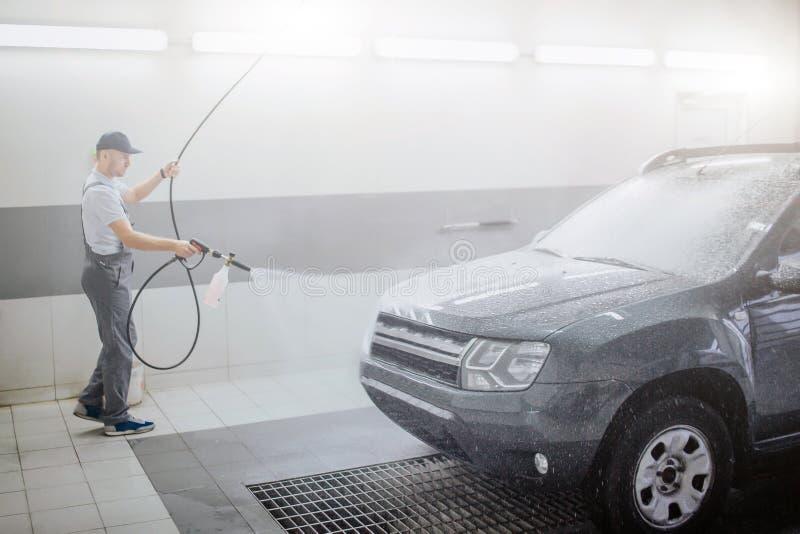 Immagine dell'automobile di pulizia del lavoratore Usa lo spruzzo d'acqua FO quello Il giovane tiene il tubo flessibile È serio e fotografia stock libera da diritti