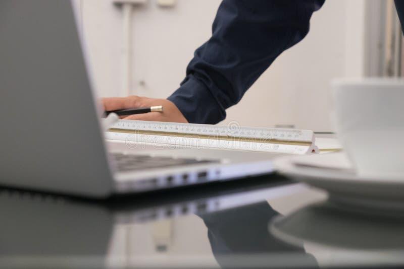 Immagine dell'ingegnere architettonica con lo sketc dei modelli e del computer portatile immagini stock