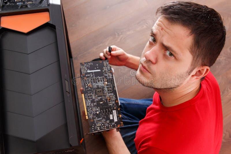 Immagine dell'uomo che esamina l'unità di elaborazione di riparazione della macchina fotografica immagini stock libere da diritti