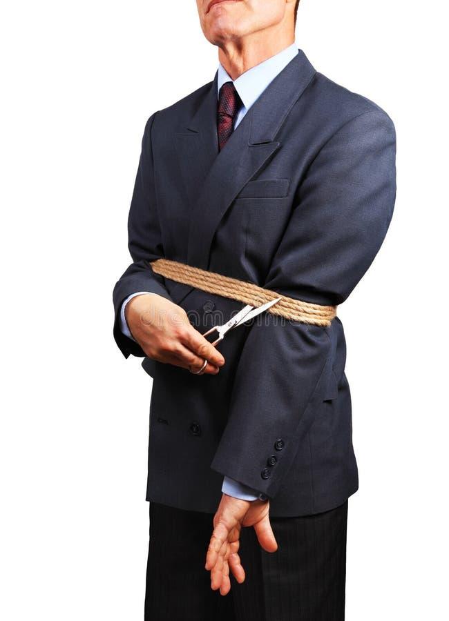 Immagine dell'uomo d'affari che prova a liberarsi dei fetters fotografia stock