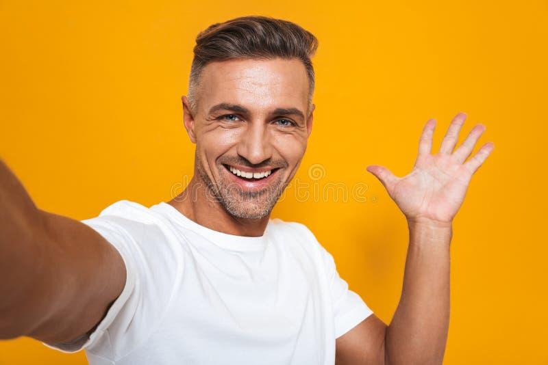Immagine dell'uomo ottimista 30s in maglietta bianca che sorride e che prende la foto del selfie fotografie stock libere da diritti