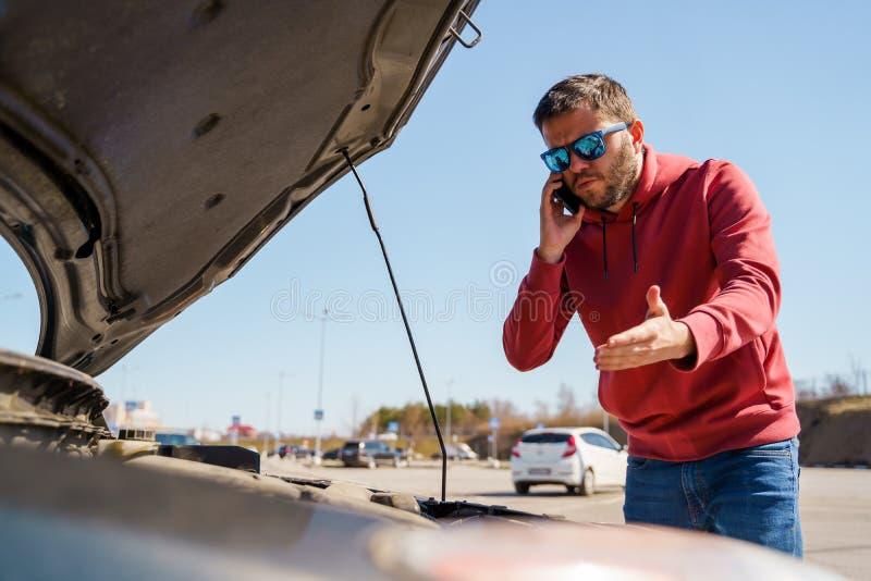 Immagine dell'uomo turbato con il telefono dentro accanto al cappuccio aperto dell'automobile rotta di giorno fotografie stock