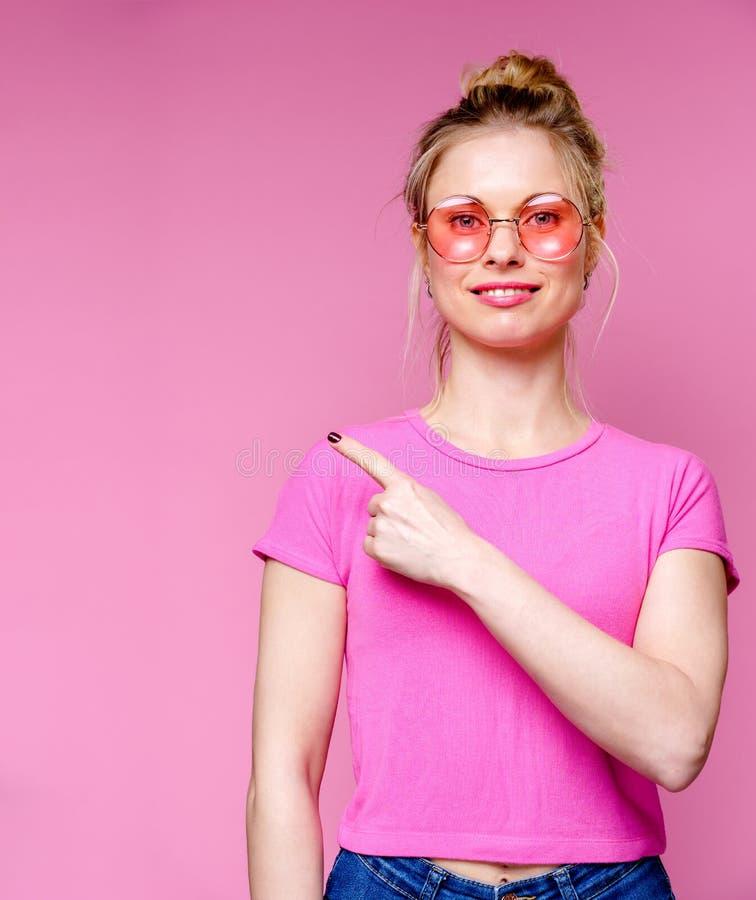 Immagine della bionda sorridente in vetri rosa che indica dito per parteggiare fotografia stock