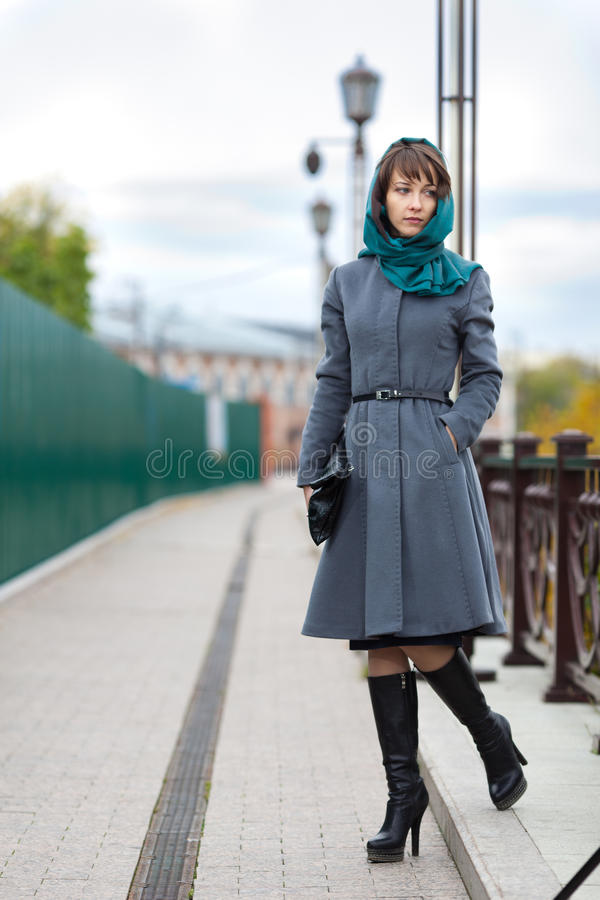 Immagine della donna in cappotto grigio che cammina sulla strada soprelevata fotografia stock libera da diritti