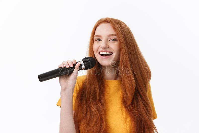 Immagine della donna felice con capelli ricci che canta mentre giudicando microfono isolato sopra fondo bianco fotografia stock