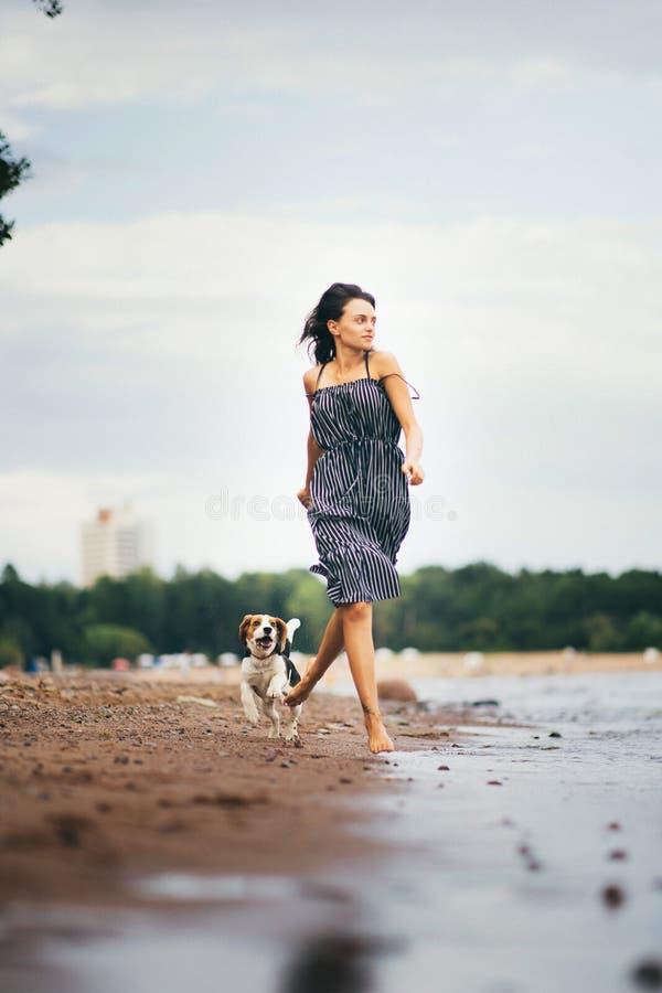 Immagine della donna felice 20s che abbraccia il suo cane mentre camminando lungo la spiaggia immagini stock libere da diritti