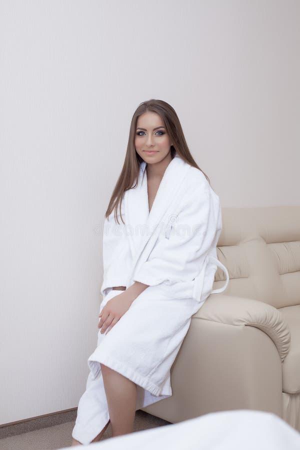 Immagine della donna graziosa in accappatoio che si siede sul sofà fotografia stock libera da diritti