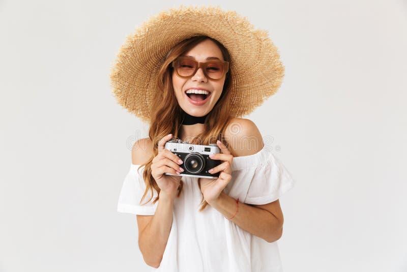 Immagine della donna 20s dei pantaloni a vita bassa di modo che indossa il grandi cappello e sole di paglia fotografia stock libera da diritti