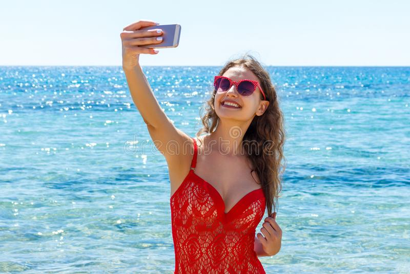 Immagine della donna sorridente felice che usando la macchina fotografica del telefono e facendo selfie fotografia stock libera da diritti
