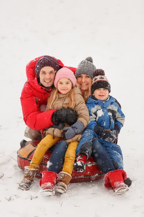 Immagine della famiglia felice con il derivato ed il figlio che si siedono sulla tubatura nell'inverno fotografie stock libere da diritti