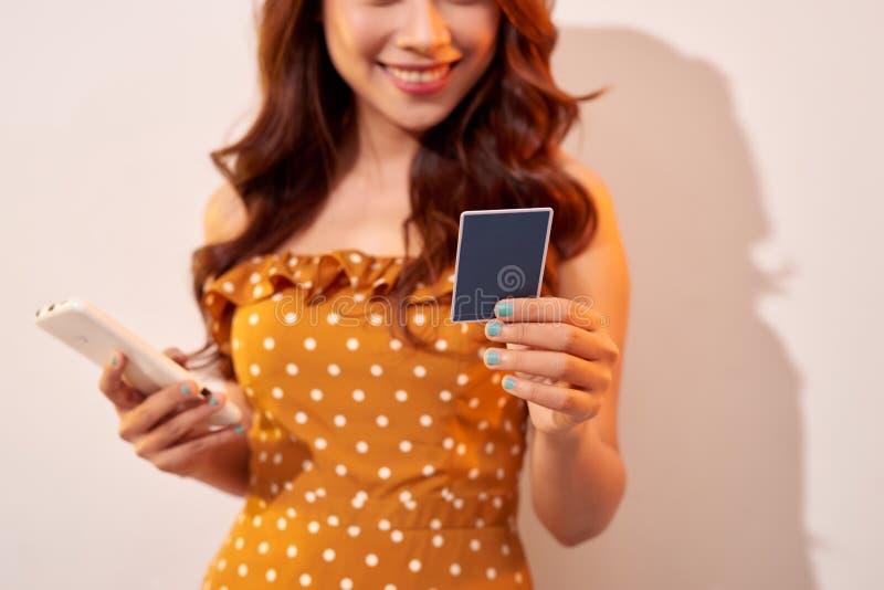 Immagine della giovane donna graziosa sveglia isolata sopra fondo beige che mostra la carta di credito di plastica mentre tenendo immagini stock