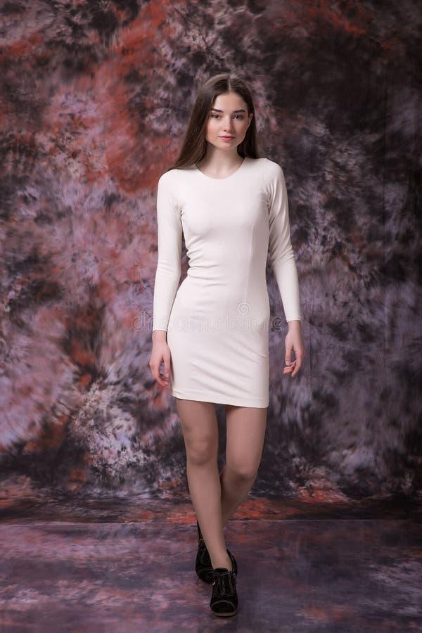 Immagine della giovane donna in vestito bianco su fondo multicolore di marmo Prova di modello fotografie stock libere da diritti