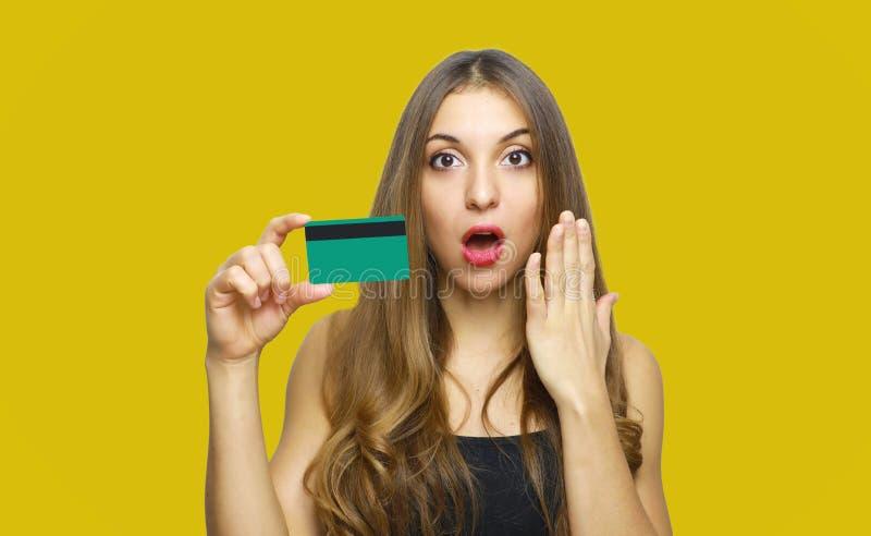 Immagine della giovane signora sorpresa che controlla fondo giallo e che tiene carta di debito in mani esaminando macchina fotogr immagine stock libera da diritti