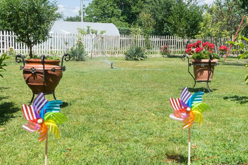 Immagine della girandola variopinta puerile sull'esterno Giardino con erba verde in un giorno di estate soleggiato Colori felici  immagine stock