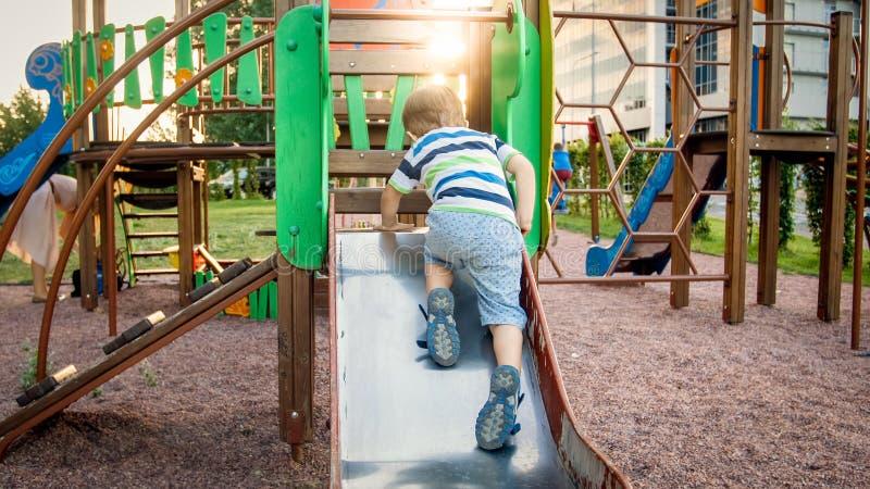 Immagine della guida allegra sorridente felice e di scalata del ragazzo del bambino sul campo da giuoco grande dei bambini al par fotografia stock