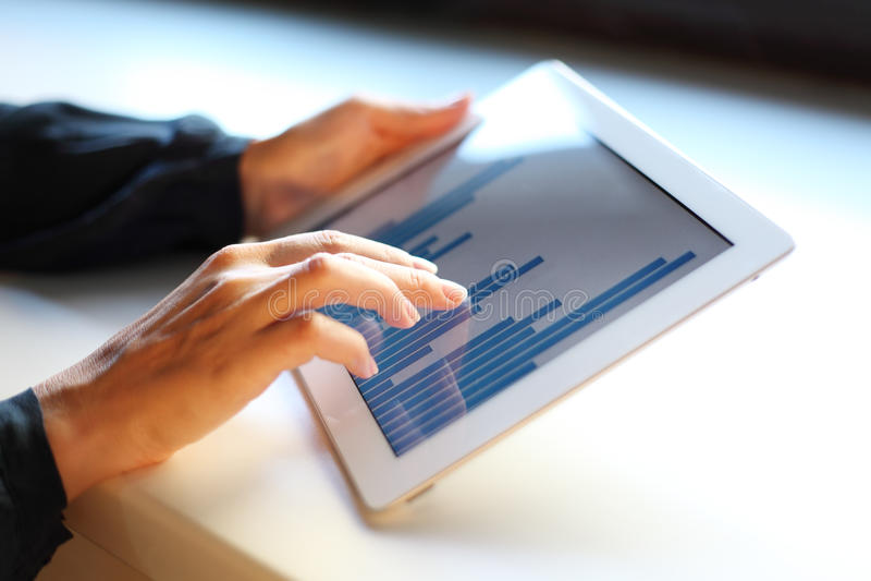 Immagine della mano della donna che indica allo schermo attivabile al tatto con il grafico commerciale immagine stock