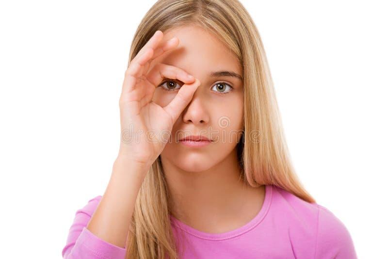 Immagine della ragazza adorabile che guarda attraverso il foro dalle dita I fotografia stock libera da diritti