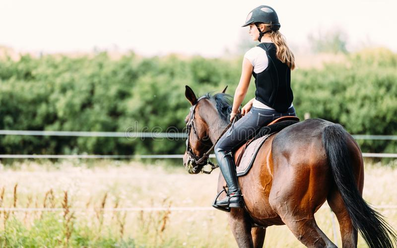 Immagine della ragazza che monta il suo cavallo fotografia stock
