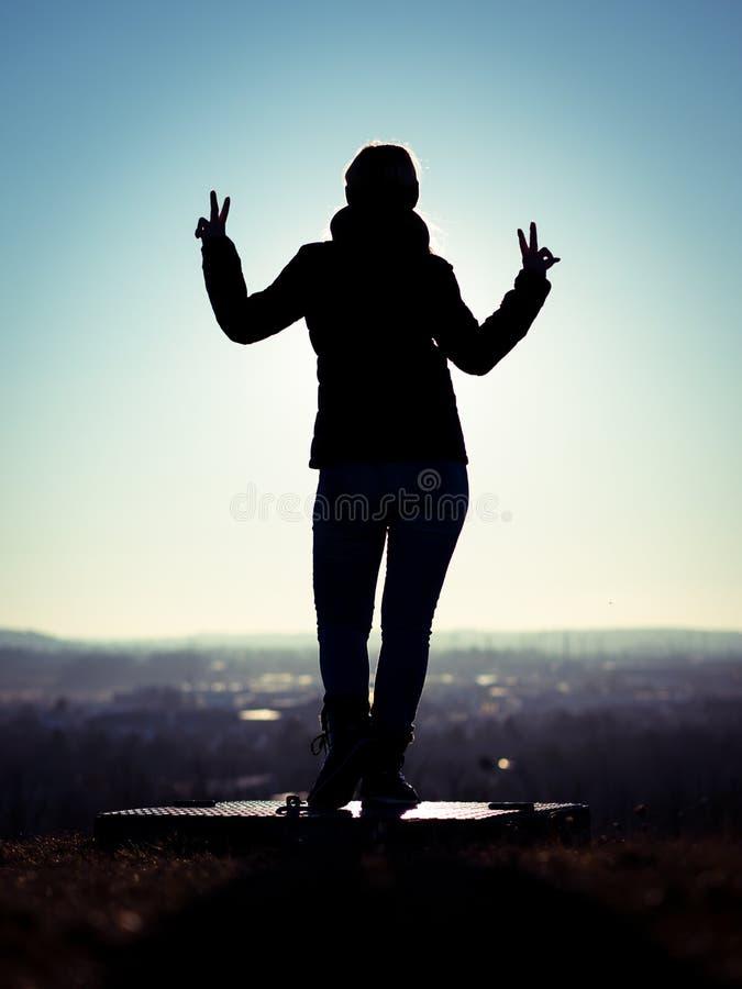 Immagine della siluetta della donna che esegue il segno di vittoria con le dita che stanno su una piattaforma immagine stock libera da diritti