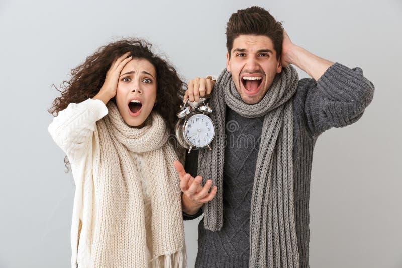 Immagine della sveglia di grido dispiaciuta della tenuta di attimo dell'uomo e della donna delle coppie, isolata sopra fondo grig fotografia stock libera da diritti