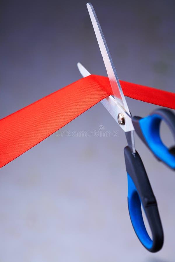 Immagine delle forbici che tagliano un nastro rosso immagini stock