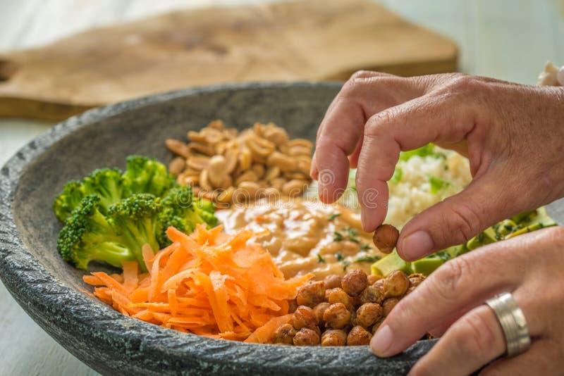 Immagine delle mani di una donna, preparante un'insalata immagine stock