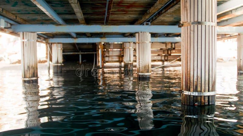 Immagine delle onde del mare e dei colums di legno sotto il pilastro alla riva di mare immagini stock