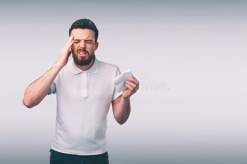 Immagine dello studio da un giovane con il fazzoletto Il tipo malato isolato ha naso semiliquido l'uomo prepara una cura per il t immagini stock