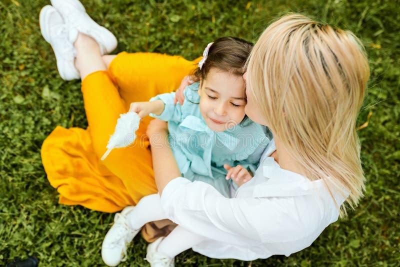 Immagine di aria aperta di bella madre che bacia e che stringe a sé con sua figlia, godente insieme del tempo immagine stock libera da diritti